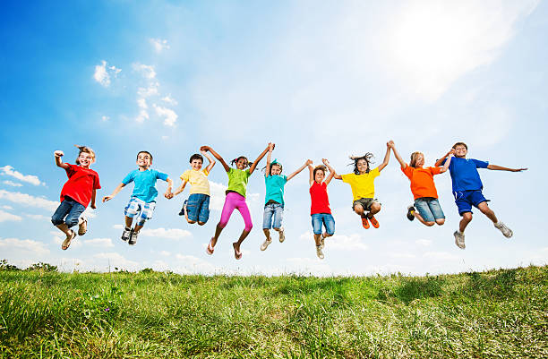 Group of kids having fun while jumping against the sky. stock photo