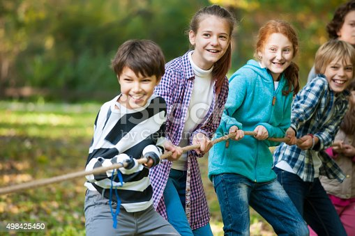 istock Group of kids in a tug-of-war game 498425450