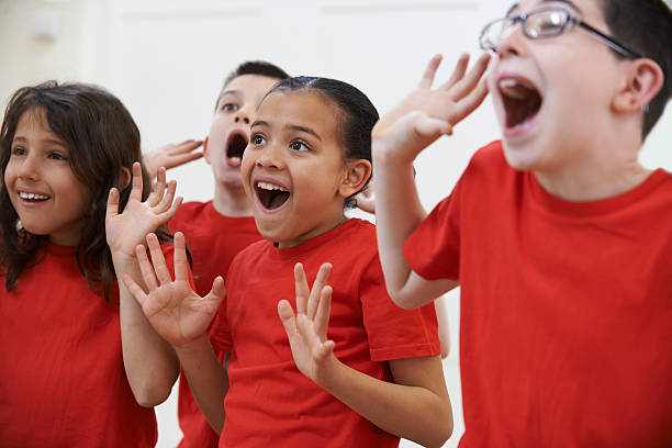 Group of kids in red shirts dramatically acting in drama Group Of Children Enjoying Drama Class Together red shirt stock pictures, royalty-free photos & images