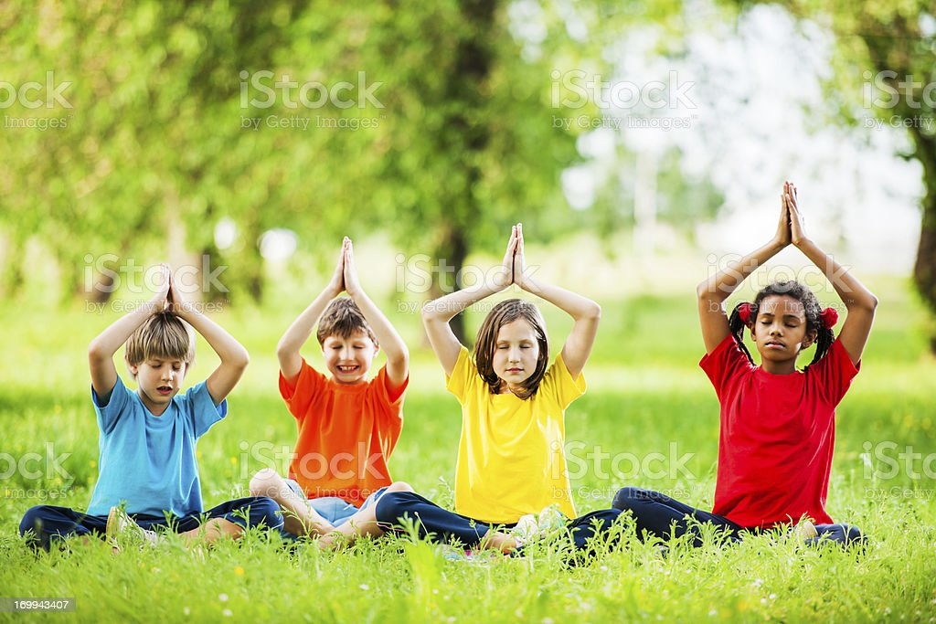Group of kids meditating with raised arms in a park. stock photo