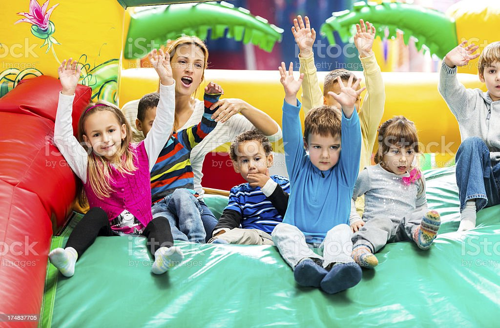Group of kids on a indoors inflatable slide. stock photo
