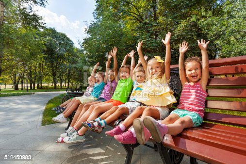 istock Group of kids on the bench cheering lifting hands 512453983