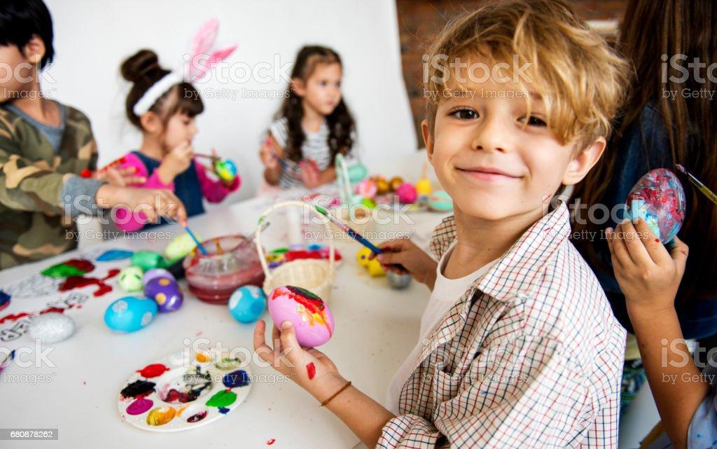 Grupo de niños pintando huevos de Pascua - foto de stock