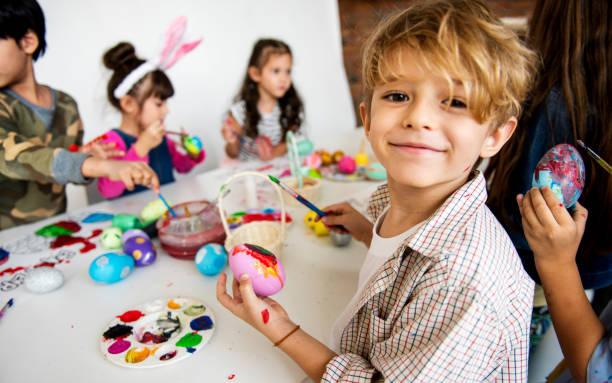grupo de niños pintando huevos de pascua - clase de arte fotografías e imágenes de stock