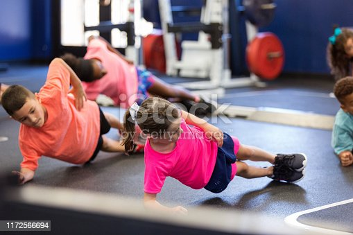 Group of children work on core strength during a fitness class for kids. They are doing side planks.