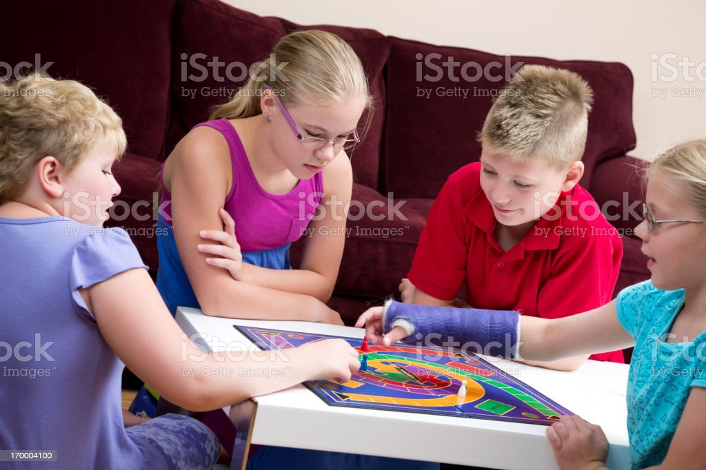 Group of kids playing board game in a living room royalty-free stock photo