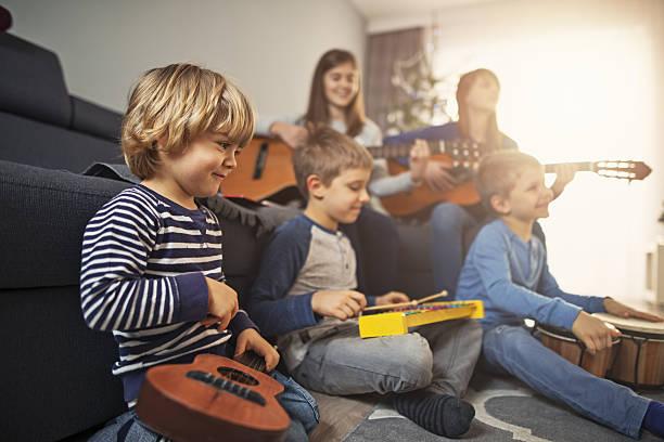 group of kids playing music together - lautbildungsspiele stock-fotos und bilder