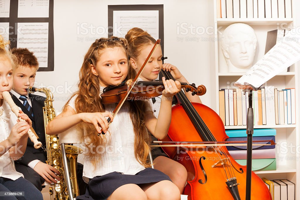 Group of kids playing musical instruments indoors stock photo
