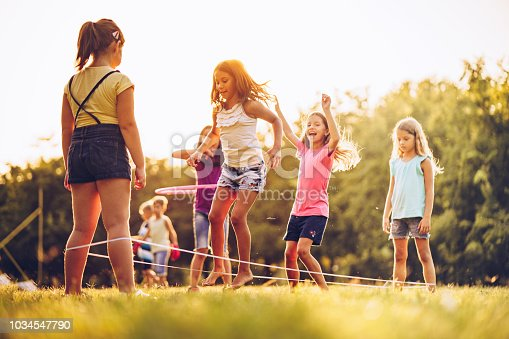 Group of children playing in public park jumping a ruber band