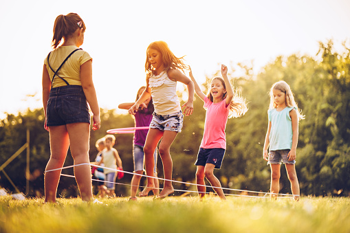 istock Group of kids playing outdoors jumping the ruber band 1034547790