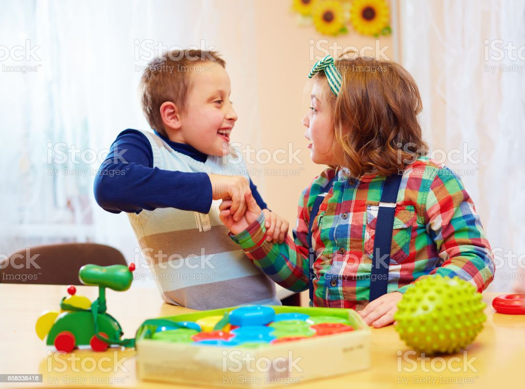 group of kids playing together in daycare center for kids with special needs - foto stock