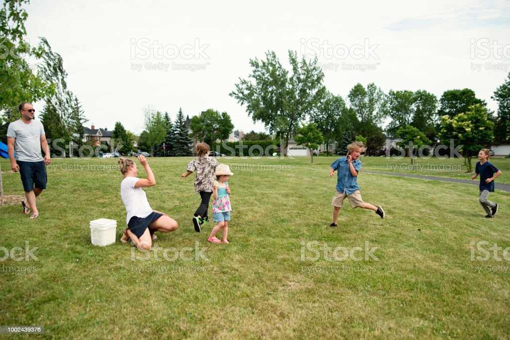 Group of kids playing with water filed balloon in suburb park. stock photo
