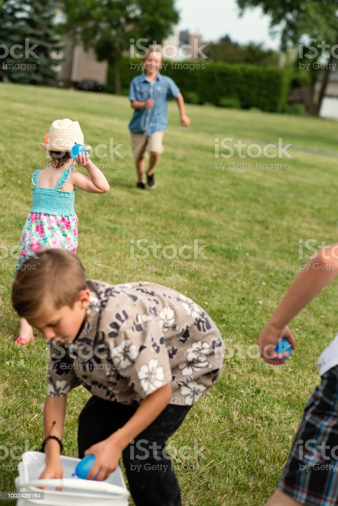 Group of kids playing with water filled ballons in suburb park. stock photo