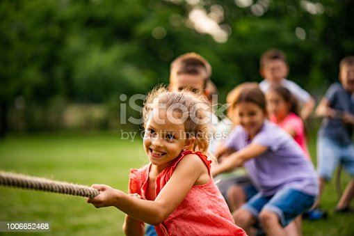 Happy kids pulling a rope in park