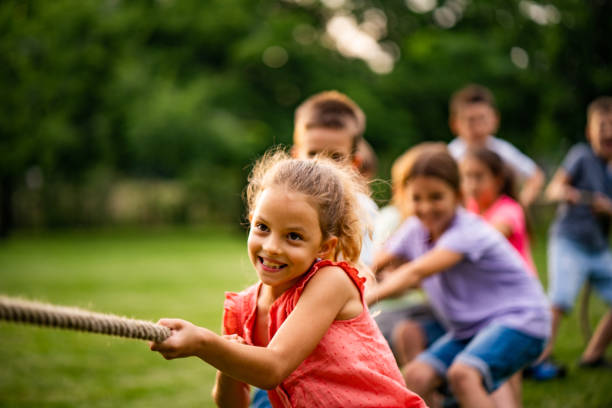 Group of kids pulling a rope stock photo