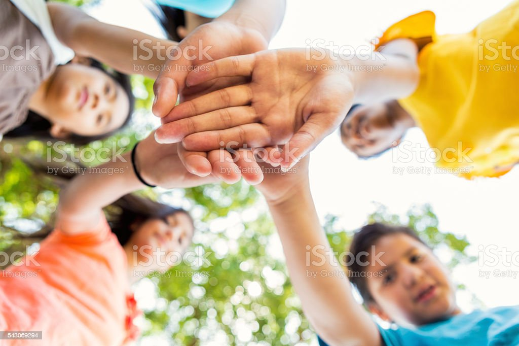 Group of kids put their hands together at park stock photo