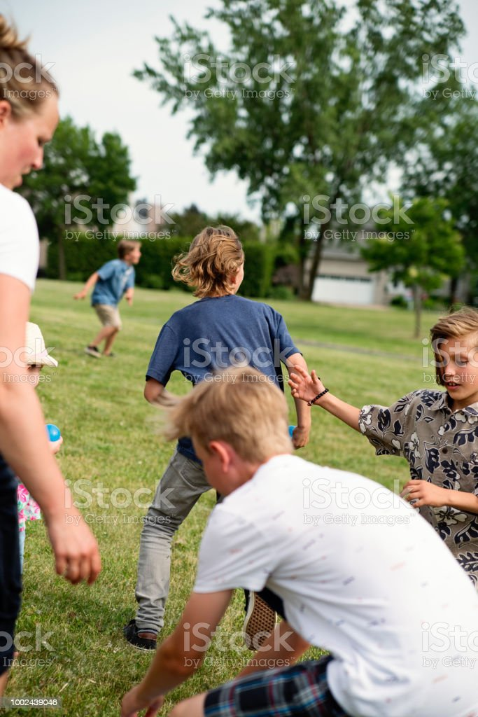 Group of kids running and playing in suburb park. stock photo