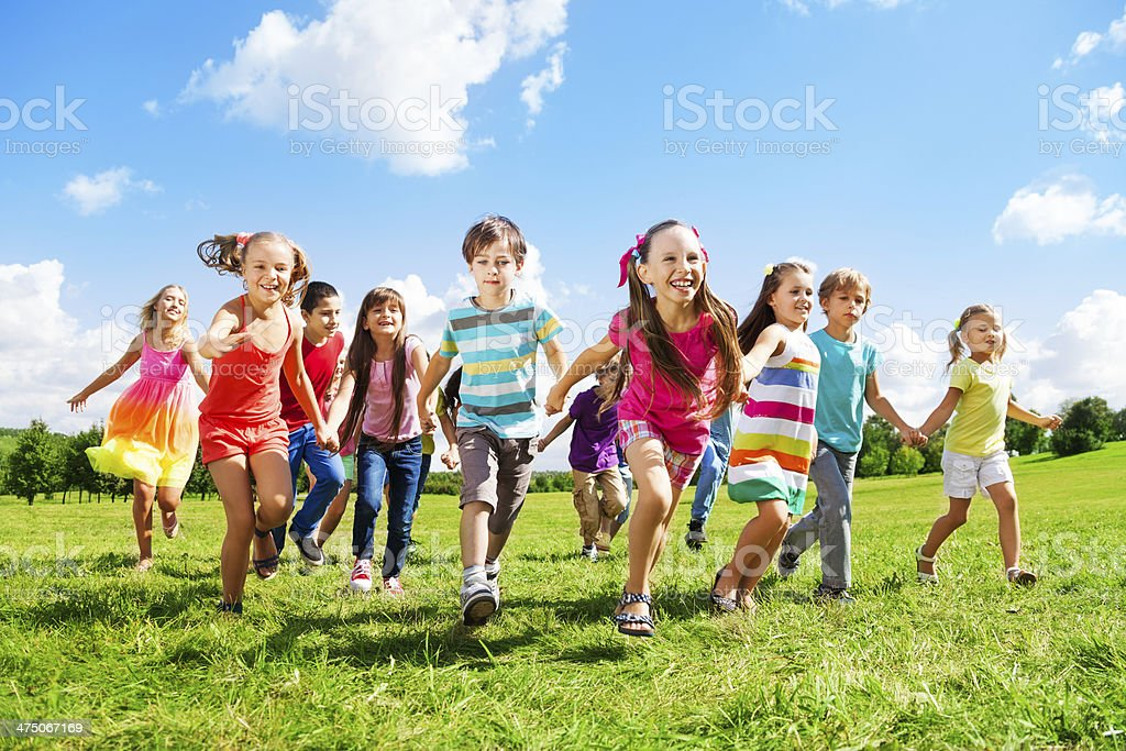 Group of kids running over grass on a sunny day stock photo