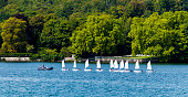 Geneva, Switzerland - August 24, 2018: Group of kids sailing boat together in a straight line at the seaside of Lake Leman, Switzerland.