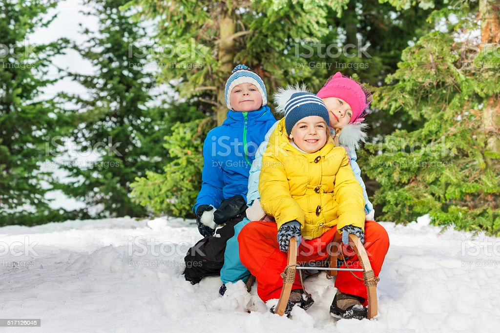 Group of kids slide down on sledge in the park stock photo