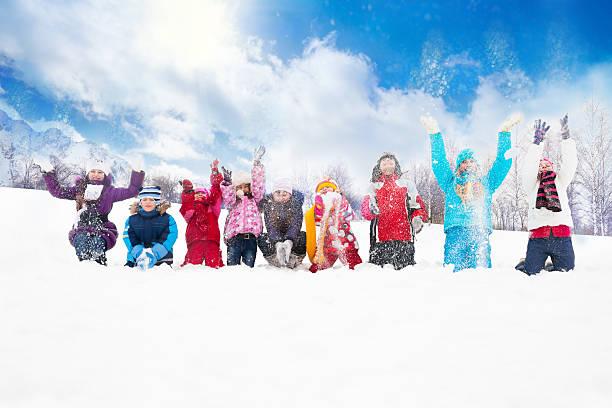gruppe von kindern werfen schnee in der luft - schneespiele stock-fotos und bilder