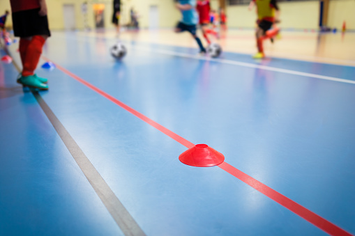 istock Group of Kids Training Indoor Soccer Futsal. Children Physical Education Class. Gym Class for Youth. Futsal Training Picture with Blurred Background 1141532394