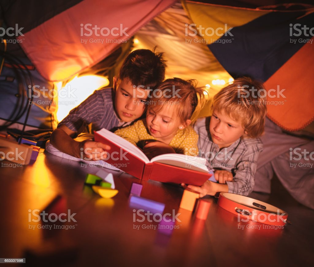 Group of kids under blanket fort reading a story together stock photo