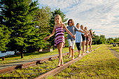Group of kids walking on a railroad track in summer.