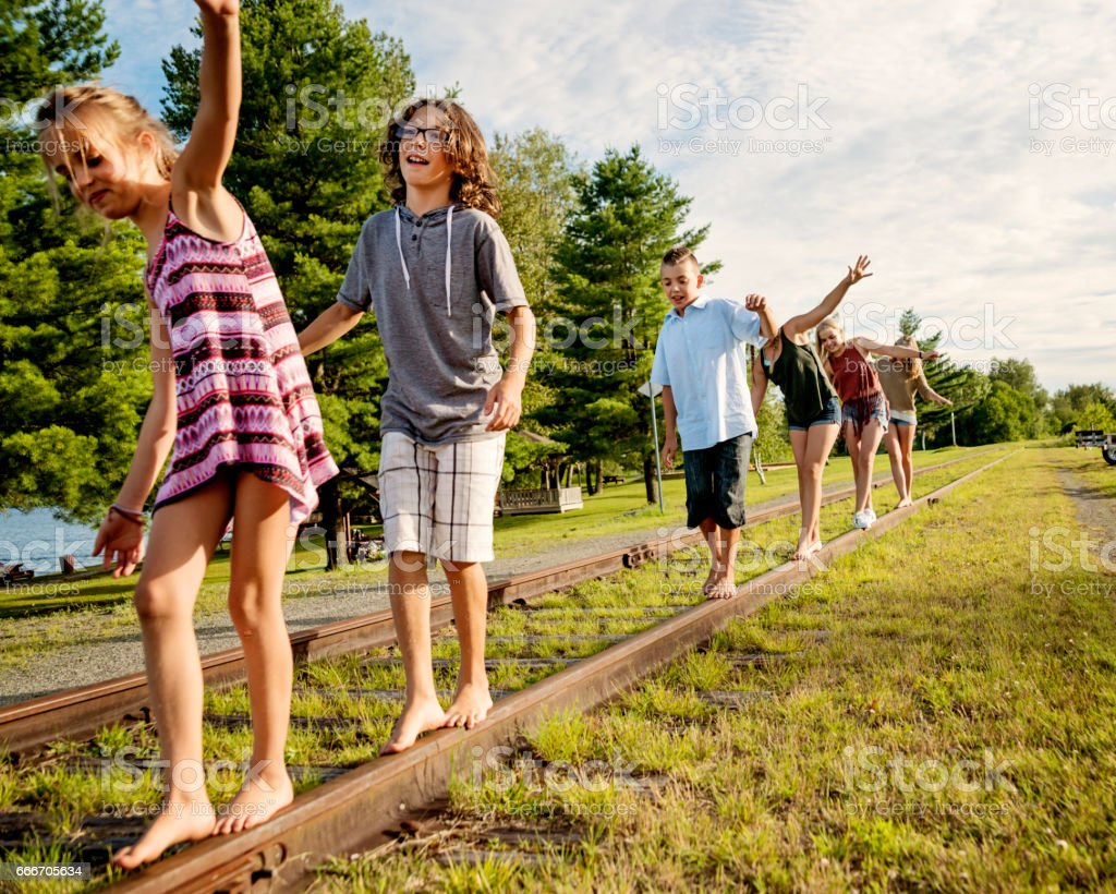 Group of kids walking on a railroad track in summer. stock photo