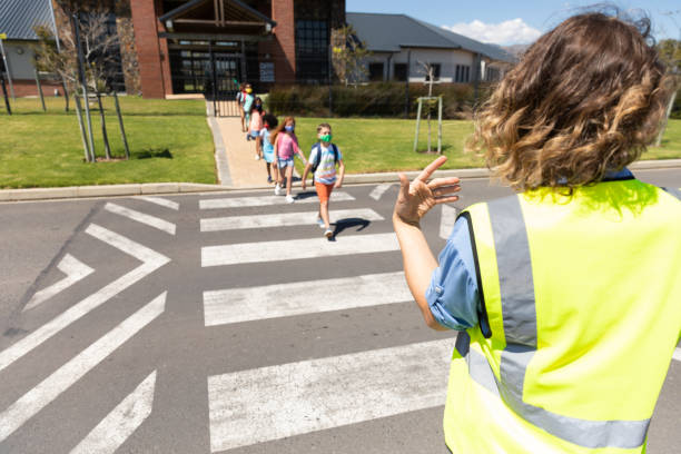 Group of kids wearing face masks crossing the road stock photo