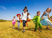 istock Group of kids with costumes running in park 513234367
