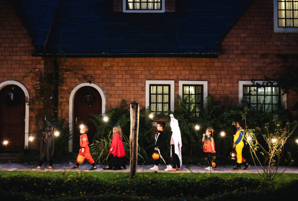Group of kids with Halloween costumes walking to trick or treating stock photo