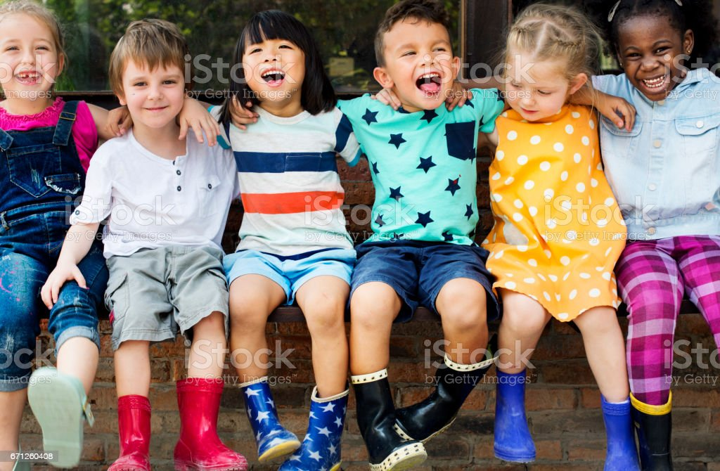 Group of kindergarten kids friends arm around sitting and smiling fun foto stock royalty-free
