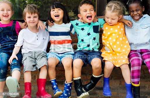 istock Group of kindergarten kids friends arm around sitting and smiling fun 671260408