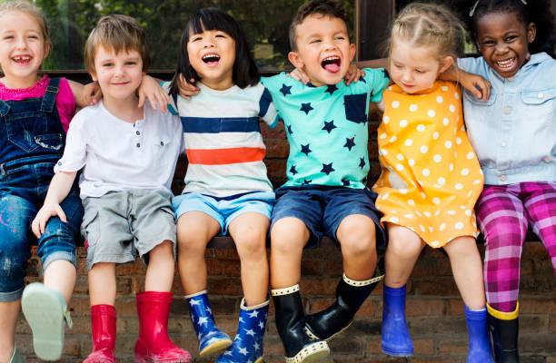 sekelompok teman anak-anak tk bersenanjat di sekitar duduk dan tersenyum menyenangkan - student study outdoor potret stok, foto, & gambar bebas royalti