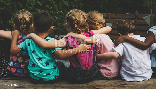 istock Group of kindergarten kids friends arm around sitting together 671260342