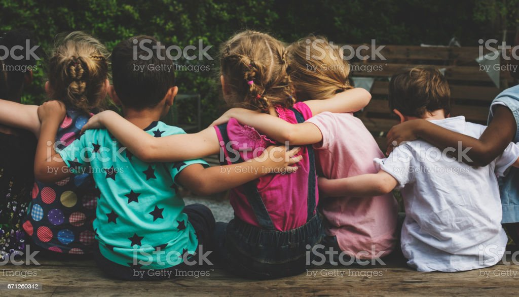 Group of kindergarten kids friends arm around sitting together стоковое фото