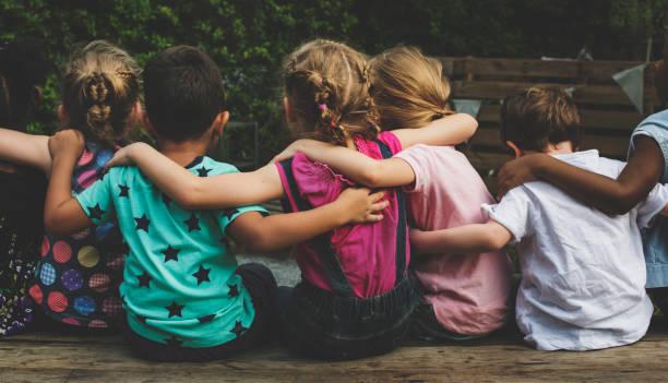 Grupp av dagis barn vänner arm runt sitter tillsammans bildbanksfoto