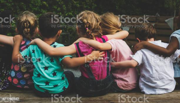Group Of Kindergarten Kids Friends Arm Around Sitting Together Stock Photo - Download Image Now