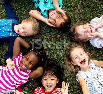 istock Group of kindergarten kids lying on the grass at park and relax with smiling 671260158
