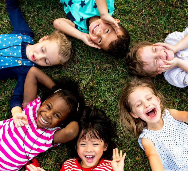 group of kindergarten kids lying on the grass at park and relax with smiling - preschool stock photos and pictures