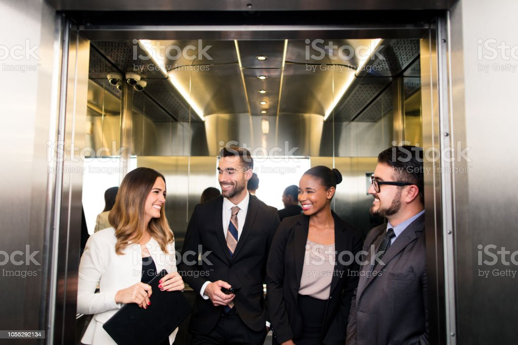 Group of latin business executives laughing in elevator stock photo
