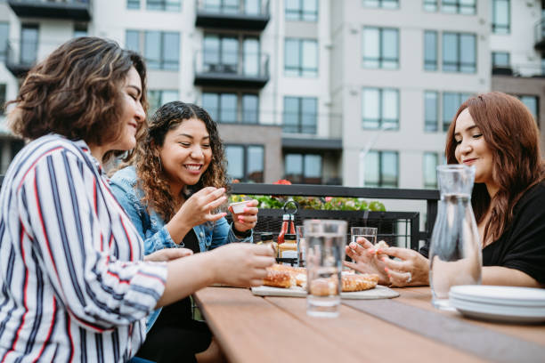 Group of Latina Friends Eat on Outdoor Patio Three Hispanic women enjoy coffee at a cafe diner, having fun sharing life experiences and memories.   Shot in Tacoma, Washington. pierce county washington state stock pictures, royalty-free photos & images