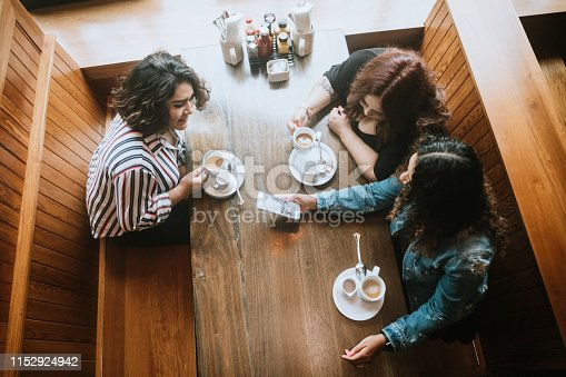 Three Hispanic women enjoy coffee at a cafe diner, having fun sharing life experiences and memories. One woman shows her friends a picture she took on her phone.  Overhead angle view.  Shot in Tacoma, Washington.