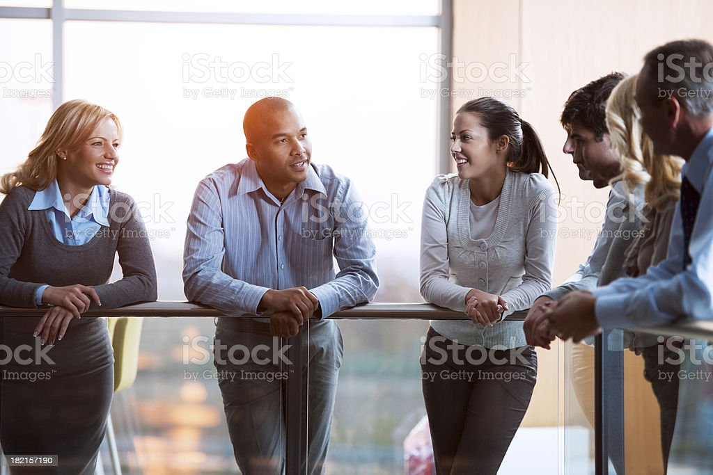 Group of laughing  businesspeople talking in a lobby royalty-free stock photo