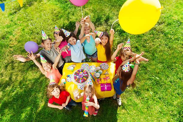 Group of laughing kids standing around B-day cake stock photo