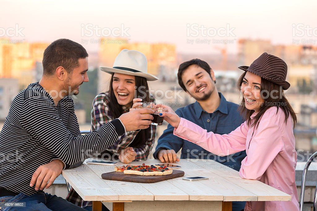 Group of Laughing People Cheers with Drinks Pizza Cafe Table stock photo