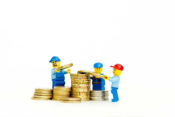 group of lego mini figure building a tower of coins. - lego house stock photos and pictures
