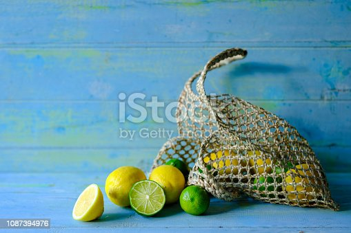 istock Group of Lemons and Limes, cross section cut and whole in a reusable hemp string basket on an old weathered vibrant blue and green abstract wooden background. 1087394976