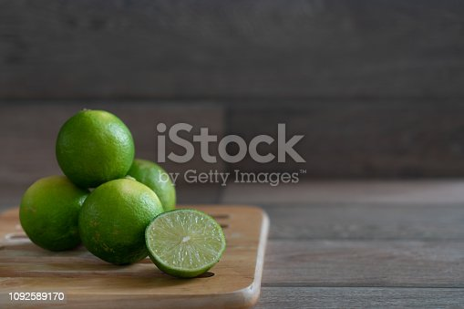 Group of limes on wooden tray on the table.